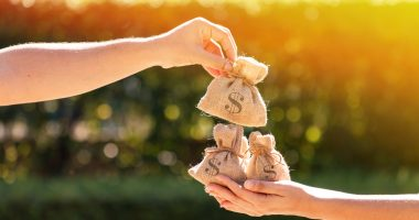 Pulnovo Medical | Pulmonary Hypertension News | Funding | Hand drops bags with dollar signs into another person's hand