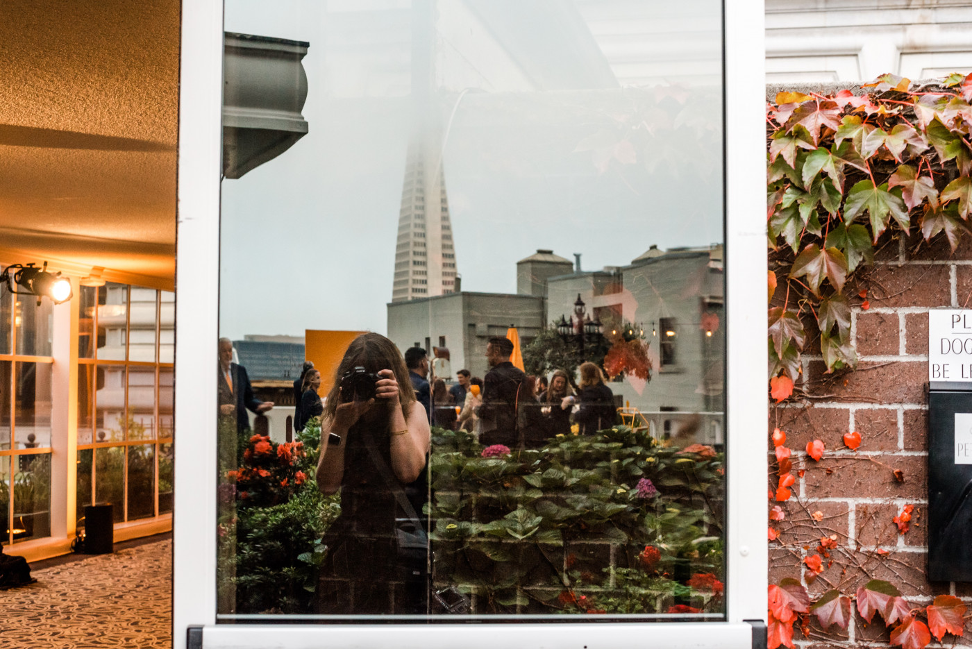 Kathleen photographing reflection in window at Fairmont hotel in San Francisco with Transamerica Pyramid behind her.