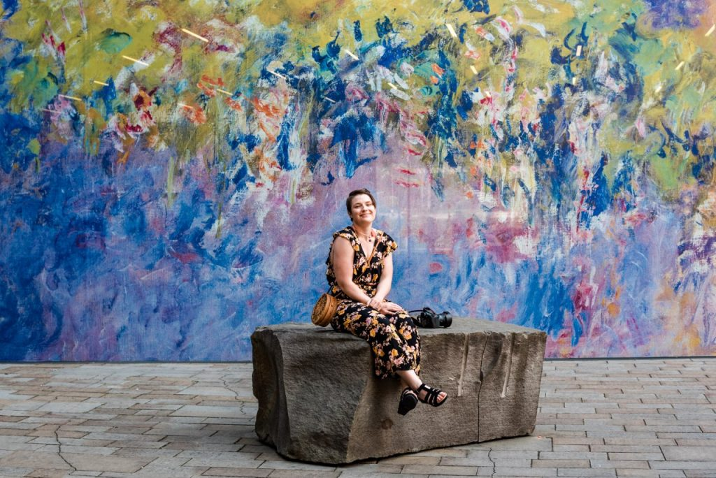 Photo of Christie sitting on a bench in front of a colorful wall at the de Young Museum in San Francisco
