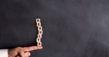 TPN171H | Pulmonary Hypertension News | Experimental Therapies | Scrabble game tiles spelling out the word 'results' stand on an extended index finger