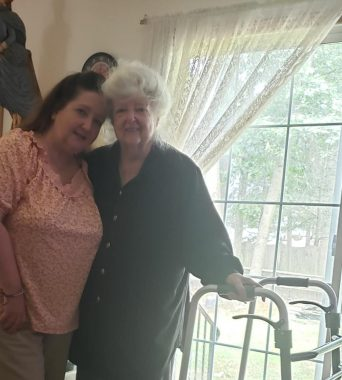 parents \ Pulmonary Hypertension News \ Colleen hugs her mom during a trip home. Colleen's mom grasps a walker with her left hand after recently fracturing her sternum during a fall.