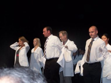 PH mother / Pulmonary Hypertension News / Sean, dressed formally, stands on stage and receives his white coat.