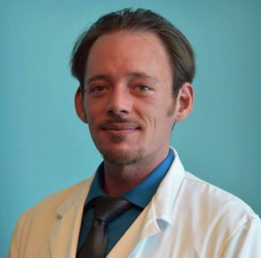PH mother / Pulmonary Hypertension News / Sean poses for a formal photo wearing his white coat.