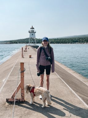 traveling with PH   Pulmonary Hypertension News   Anna stands with her dog next to the water at the North Shore.