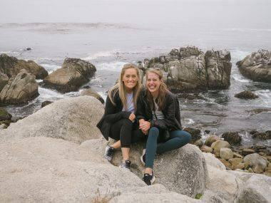 traveling with PH   Pulmonary Hypertesion News   Anna and her sister pose on a large boulder next to the ocean in California