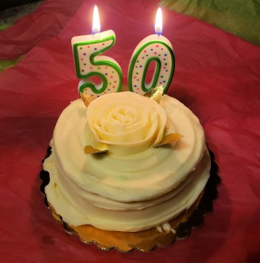 50th birthday   Pulmonary Hypertension News   A birthday cake with lit candles indicating 50 sits atop a table with a red tablecloth